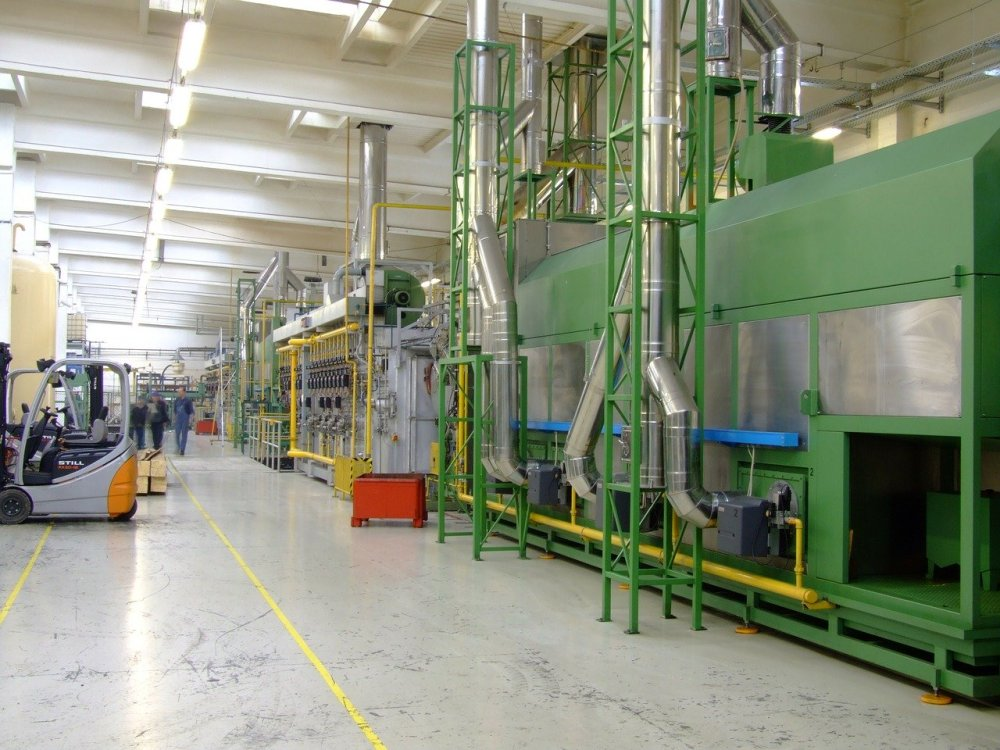 A factory hallway with large green and grey machinery on the right side, a forklift on the left, and several workers walking in the distance