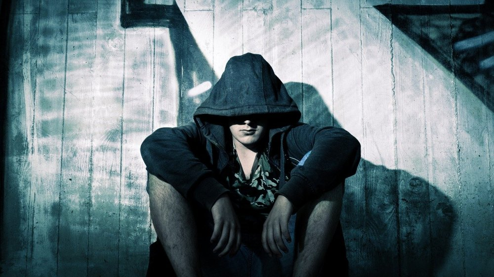 A blue tinted photo of a young caucasian man with arms resting on his knees seated against a white fence with some graffiti, while wearing a hoodie with the hood over most of his head