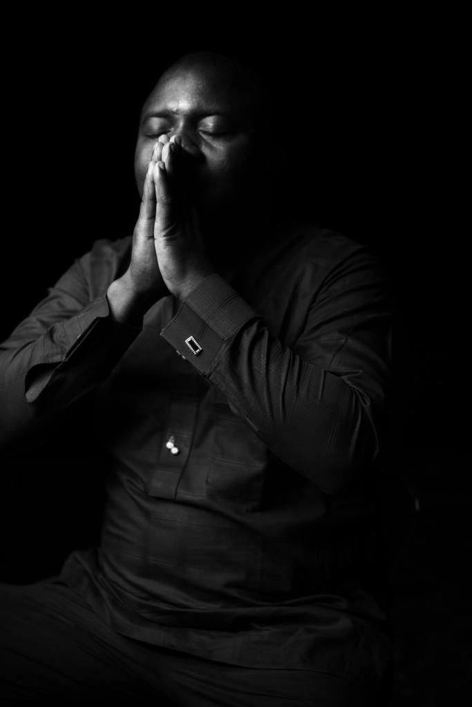 A black and white photo of a man of color wearing a dark long sleeved shirt with his hands folded in front of his face and his eyes closed in apparent prayer