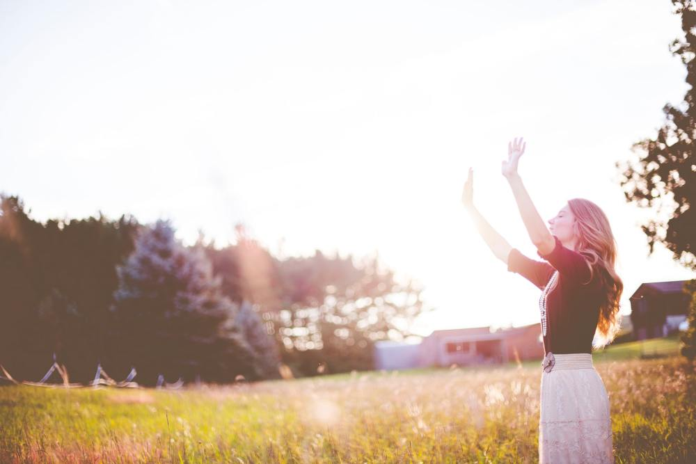 A photo of a woman on the right side of the picture with arms raised, eyes closed, and standing over a grassy field with trees and farm buildings in the distance and a bright sun overhead