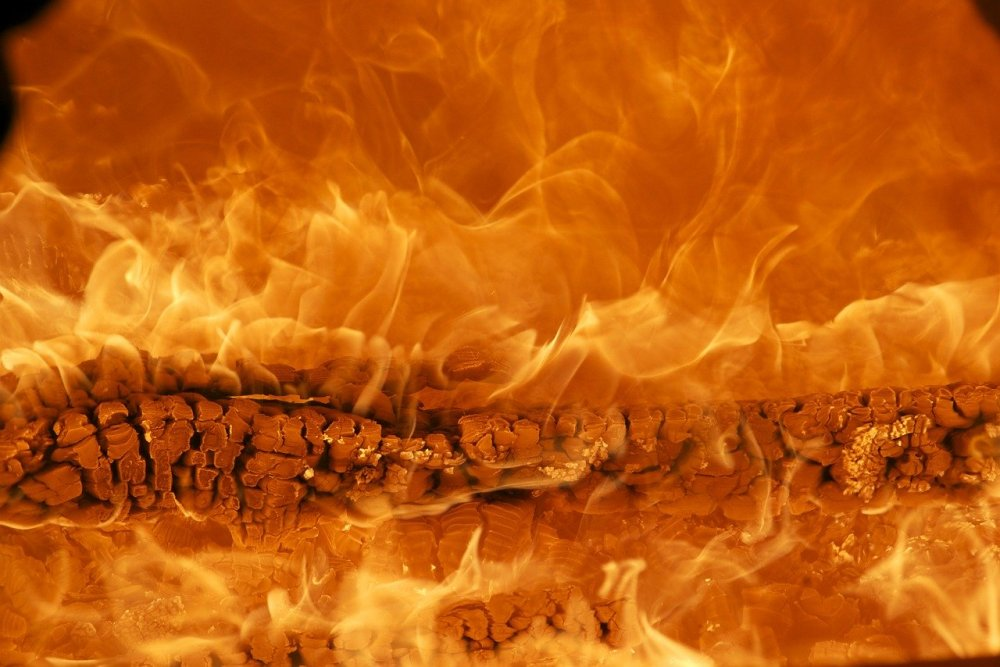 A photo full of intense flames emanating from a burning log in the center of the picture