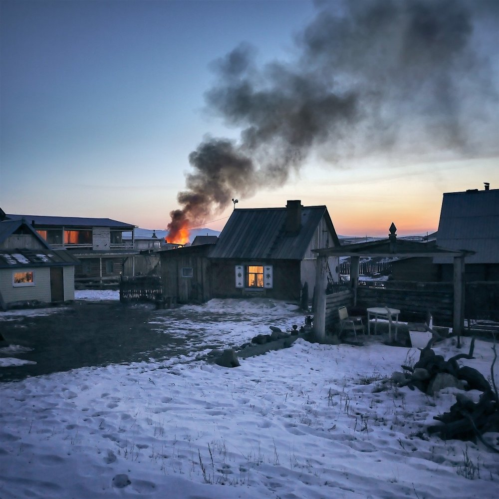 Flames and smoke rising in the distance of small Siberian village with snow on the ground a fading sunset in the background