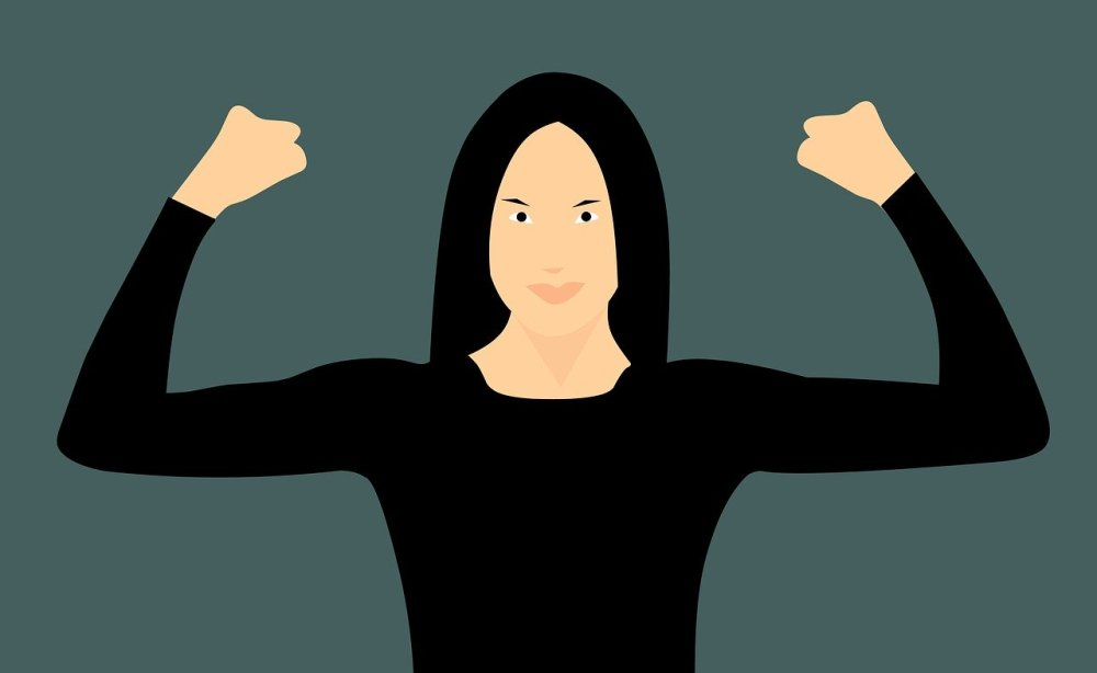 A graphical image of a caucasian woman in black with black hair holding her arms and clenched fists in the air with a serious smile on her face