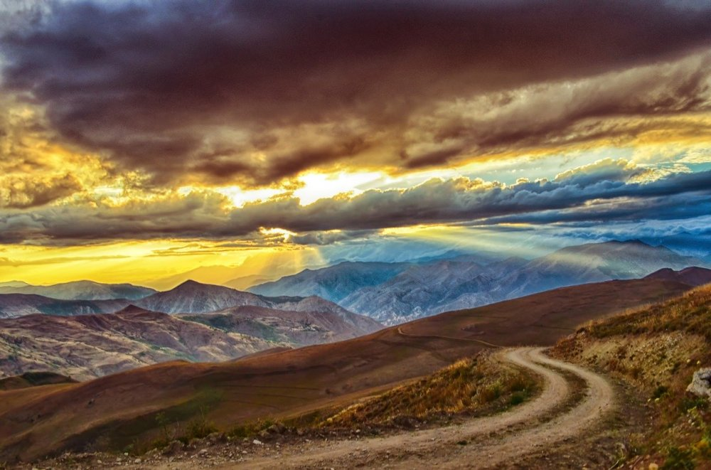 A winding dirt road leading out of a series of brown rolling hills and grey mountains with a mixture of grey/brown, blue and yellow clouds and sky overhead along with beams of sunlight poring through