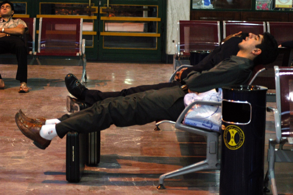 A caucasian man lying in a chair, asleep, in an airport terminal with his legs propped up by a piece of luggage