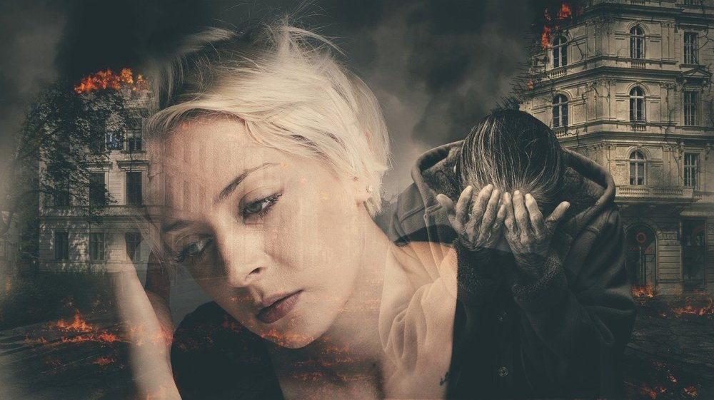A composite photograph of a middle aged Caucasian woman with white hair and a black shirt leaning toward her raised right hand surrounded by black and white images of old buildings on fire and a older woman wearing a hooded jacket with her head resting in her raised hands