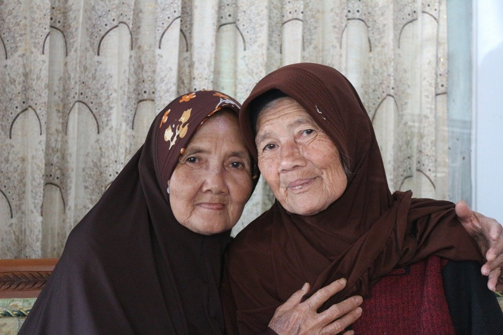 A photographic portrait of two older Asian woman wearing hooded garb with one partially embracing the other in front of a pleated white patterned curtain