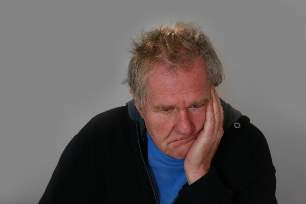 A older caucasian man wearing a black jacket and blue t-shirt seated with his left hand pressed against the side of his face in a sad, disturbed expression