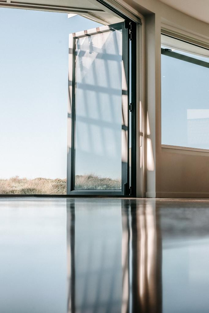 A ground level photo of a glass door opened to the outdoors and reflecting on the glossy floor
