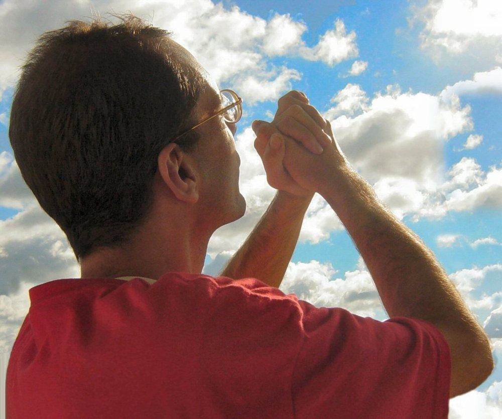 The partial back side of a Caucasian man with dark hair, glasses, and a red short sleeved shirt holding his clinched hands together in the air towards a the sun and a partially cloudy sky