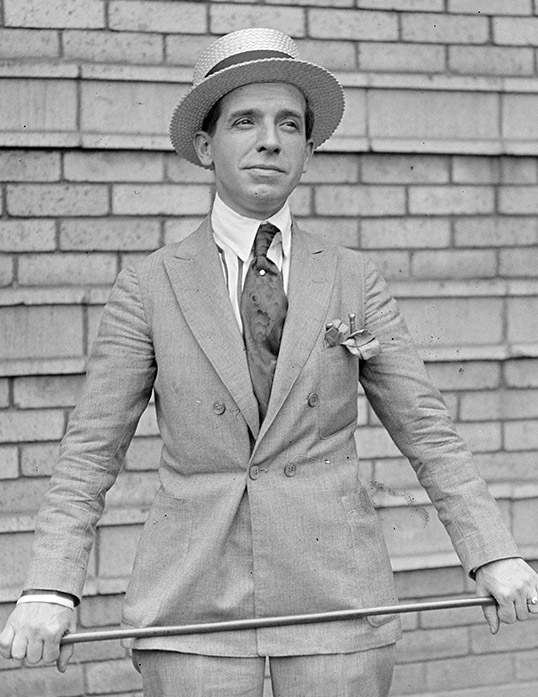 A black and white photographic portrait of Charles Ponzi standing against a brick wall holding a bar at waist level