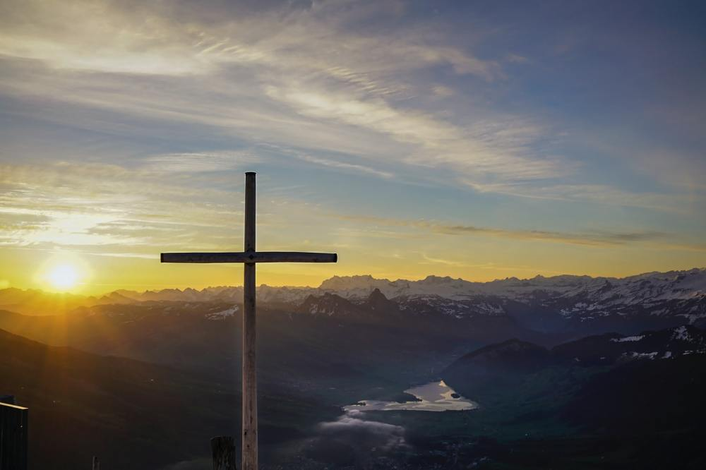 A cross on a mountainside overlooking a river and other mountains in the distance with a yellow sun setting in the background under a blue partly cloudy sky