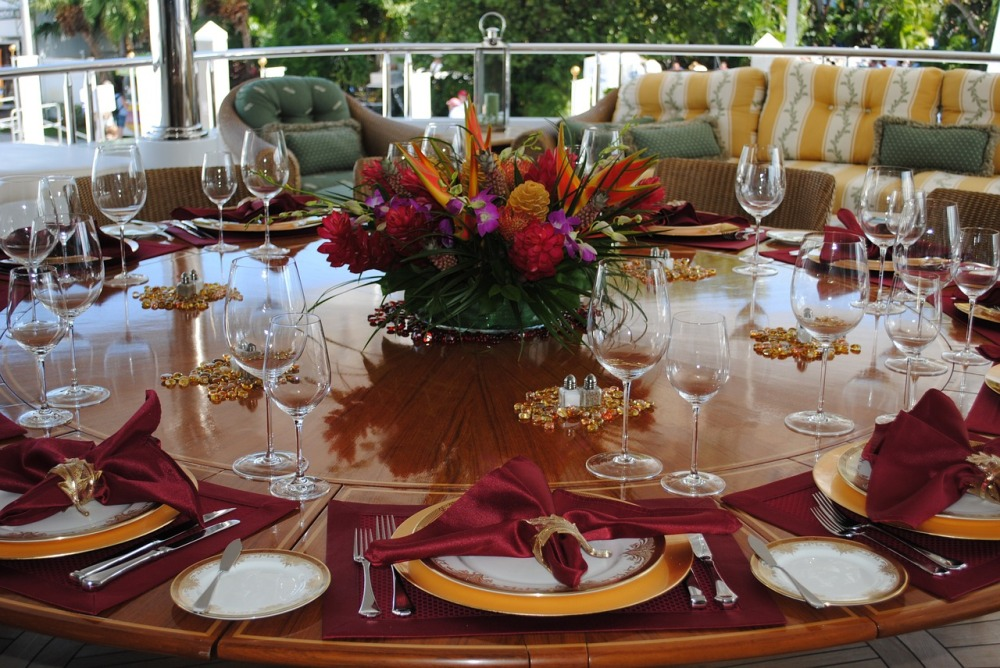 A large round table set with elegant glassware, fine china, and a colorful floral centerpiece in a covered outdoor dining area with outdoor furniture in the background