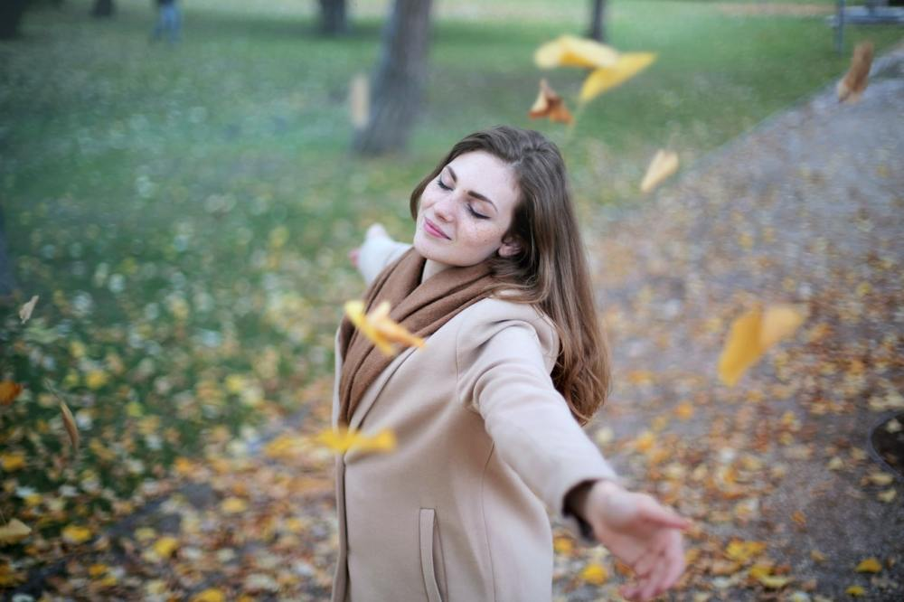 A young woman with long brown hair wearing a beige sweater and a brown scarf holding her arms out at shoulder level and eyes closed while standing on a leaf strewn path with grass in the background and yellow leaves falling