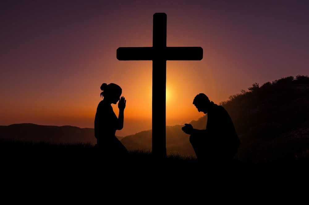 A silhouette of a man and a woman kneeling in prayer at a cross with a rising sun, hills, and trees in the background