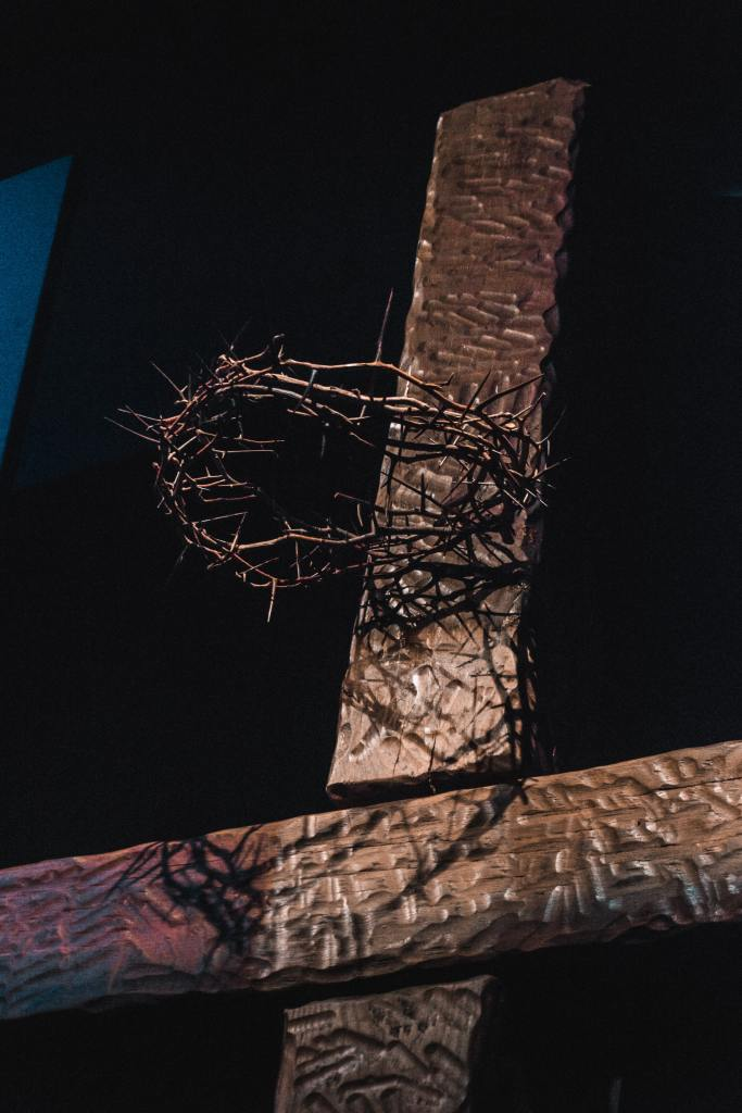 Closeup photo of the upper portion of a wooden cross on a black background with a crown of thorns attached near the top