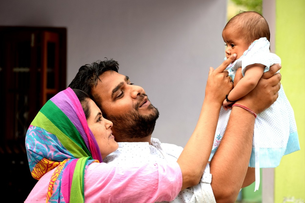 A young Indian couple holding a child in the air and smiling