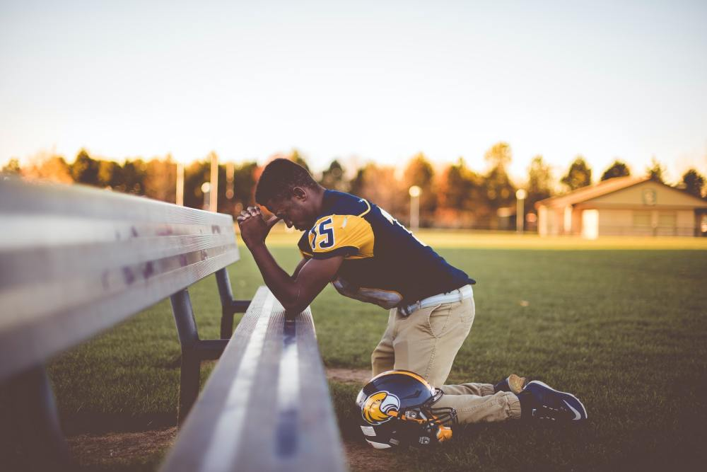 An African-American football player in full yellow and black uniform with tan pants and helmet near his leg kneeling in prayer on a metal bench with blue sky, sunlit trees and a building in the distant background