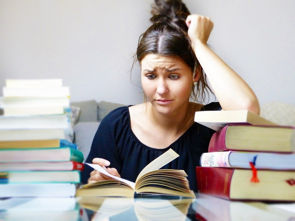A young woman with black hair and a black short sleeved shirt sits at a table filled with stacks of books staring incredulously, with her left arm resting on a small pile of book and leaning on her head, at an open book laying flat in the table