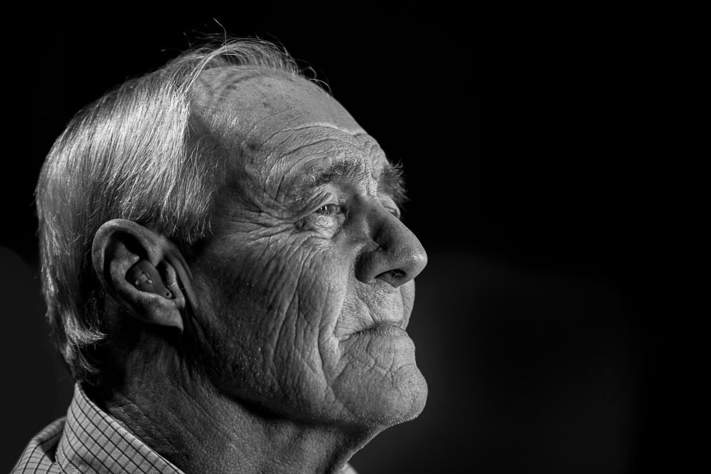 A black and white side portrait of an elderly gray haired caucasian man wearing a hearing aid on a black background