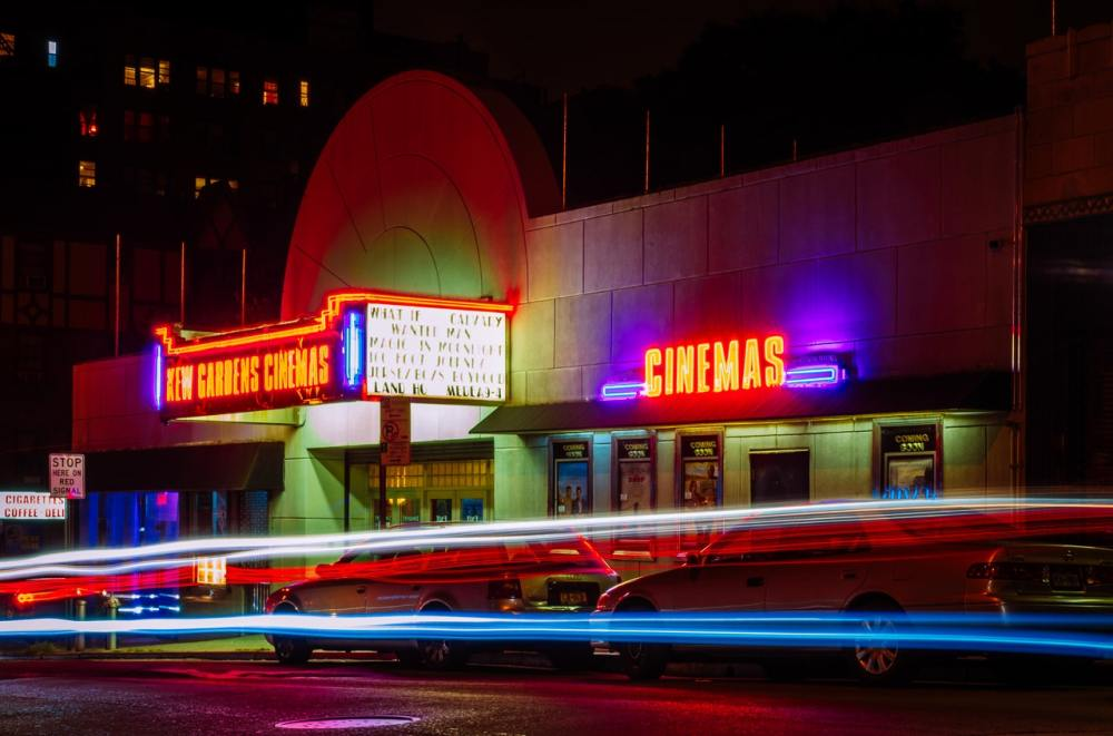 Night view of a movie theater exterior with neon lights displaying the theater's name and streaks of light from passing vehicle tail and headlights
