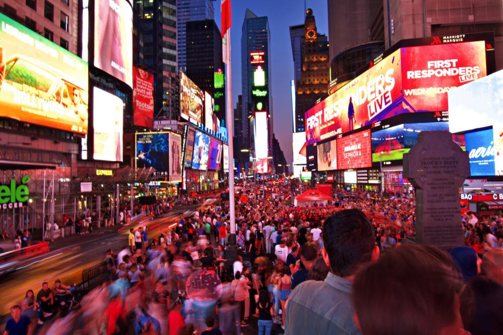 A photo looking down Times Square in New York City at night with hundreds of people and brightly lit full colored electronic billboards on the buildings of both sides of the street