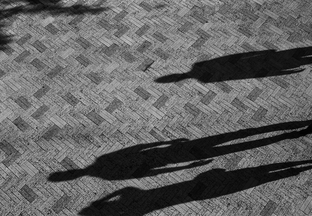 A black and white photo of three long shadows of human figures on top of a brick patterned walkway