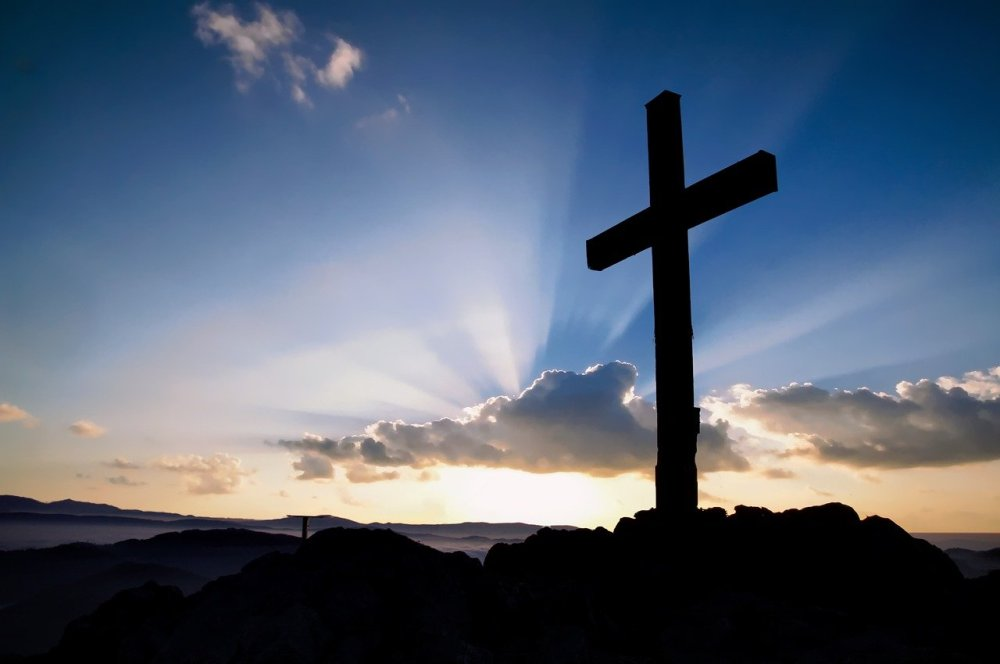 A silhouette of a large cross, on a rocky surface, on the right side of a photo with blue sky, assorted clouds, a setting sun with beams protruding out