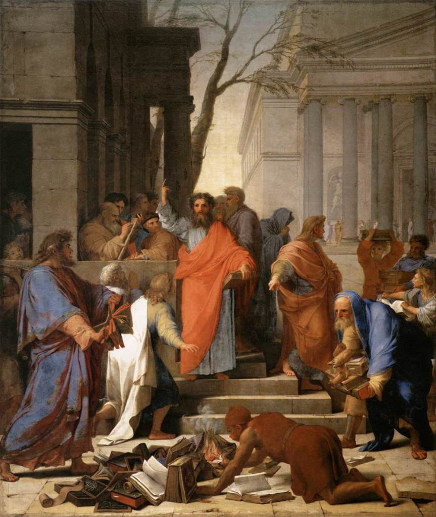 A painting of the Apostle Paul, by Eustache Le Suer, standing with an orange tunic, one arm raised and the other holding a book amidst a crowd of assorted individuals and a small pile of books the foreground beginning to be burned