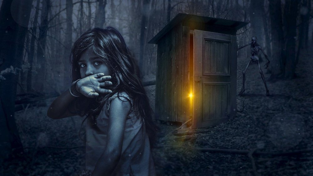 A grayscale image of young Caucasian girl looking towards the camera with the backside of her hand raised against her mouth while crouched near a wooden shed with the door partially open and a yellow light shining bursting out as well as a skeleton standing in the near distance behind it in the midst of a forest