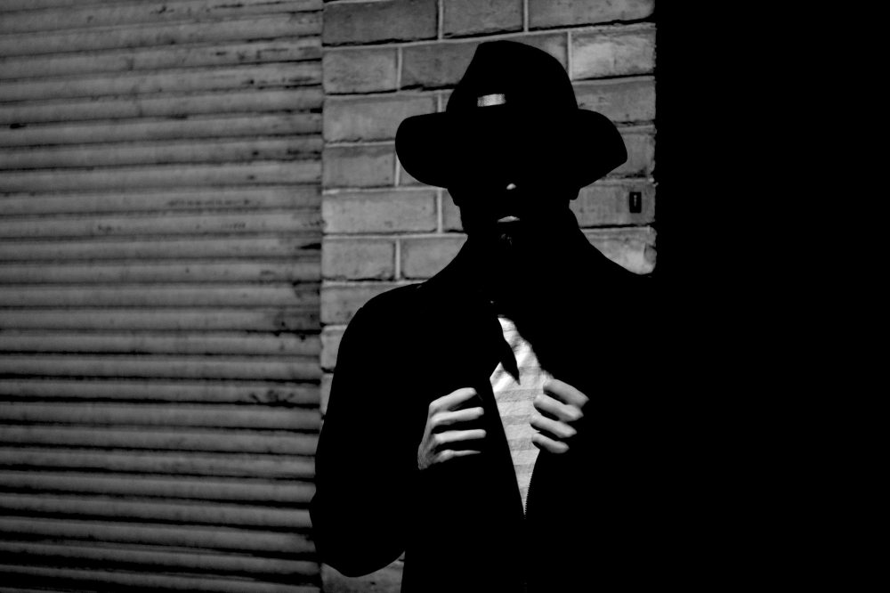A black and white photo of a man wearing a black narrow brimmed hat, dark jacket, partially exposed white striped shirt with hands pulling it open while standing against a brick wall next to a corrugated roll-up door