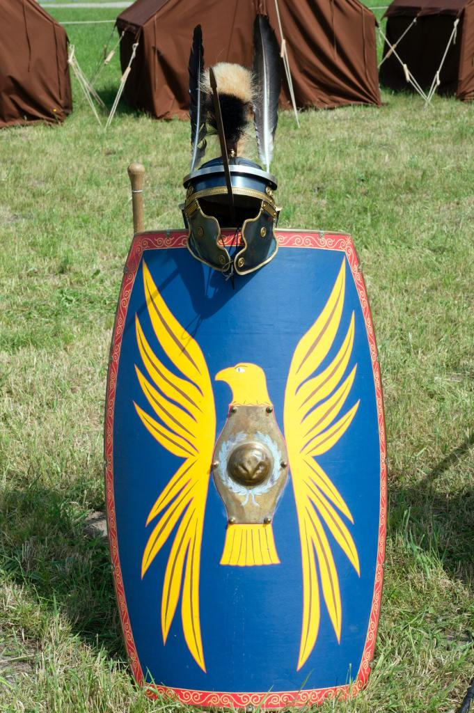 Photo of a blue Roman/medieval shield with a red decorative border and a large yellow eagle crest resting on the ground with a helmet attached to the top and brown tents in the background