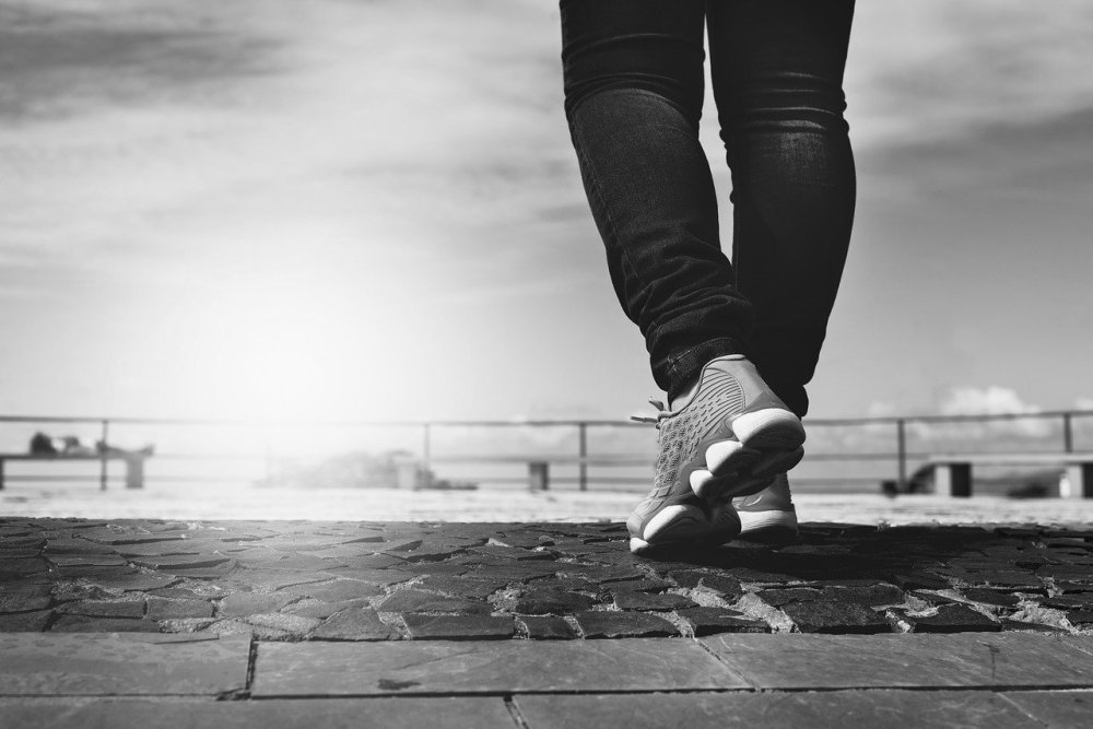 A black and white photograph of a person in dark pants wearing athletic shoes walking on a stone inlaid platform with bright sun and and a railing in the distance