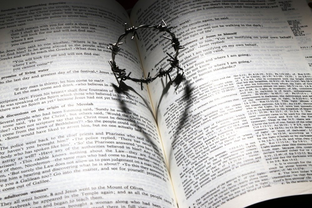 A small ring of barbed wire resting vertically in the fold of an open Bible casting a heart shaped shadow