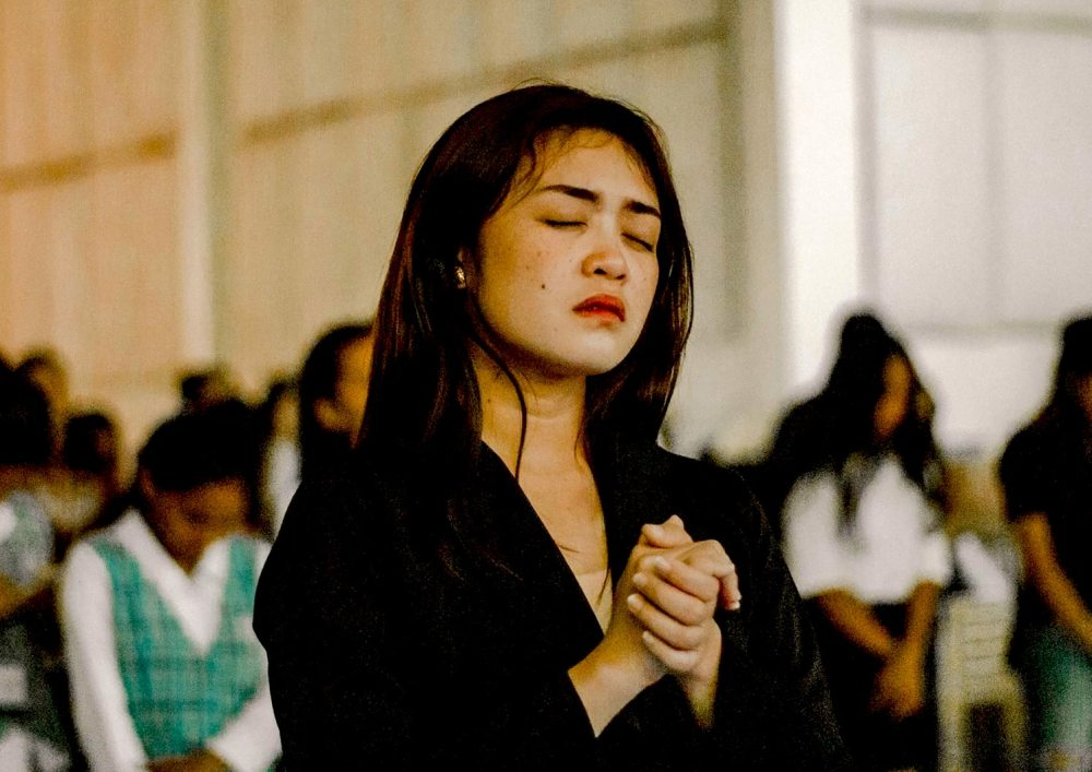 A young Asian woman standing with her eyes closed in prayer with others in the background doing the same