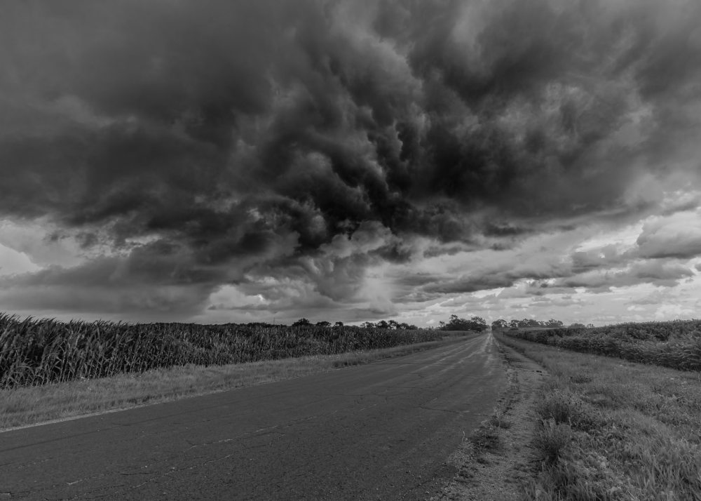 A black and white photo of approaching storm clouds alongside a small two-lane rural road between two sections of farmland