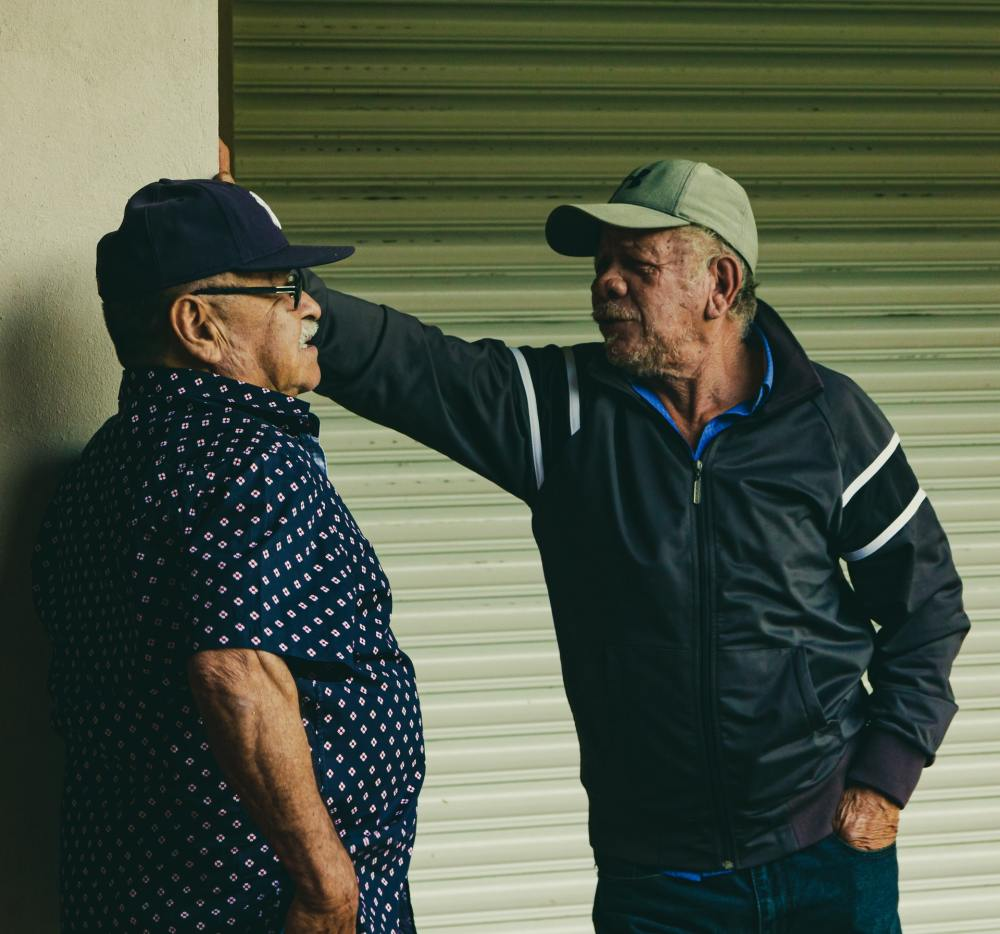 Two older Hispanic men standing in front of a light green roll-up door while talking