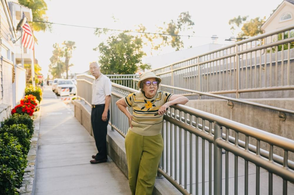 An elderly woman wearing a hat and a light green striped shirt with a single yellow flower and olive green slacks facing slightly toward the camera while leaning on a railing of a disability ramp in a sunlit suburban community with an elderly man standing behind her in a white shirt and dark pants and a somewhat incredulous expression on his face