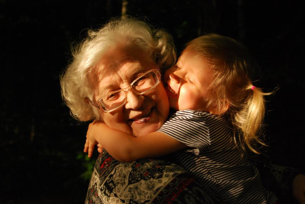 A head shot portrait of a smiling elderly woman with glasses and white hair holding a blond-haired young girl in her arms with the girl's arms wrapped around her neck and sunlight streaming on both of them