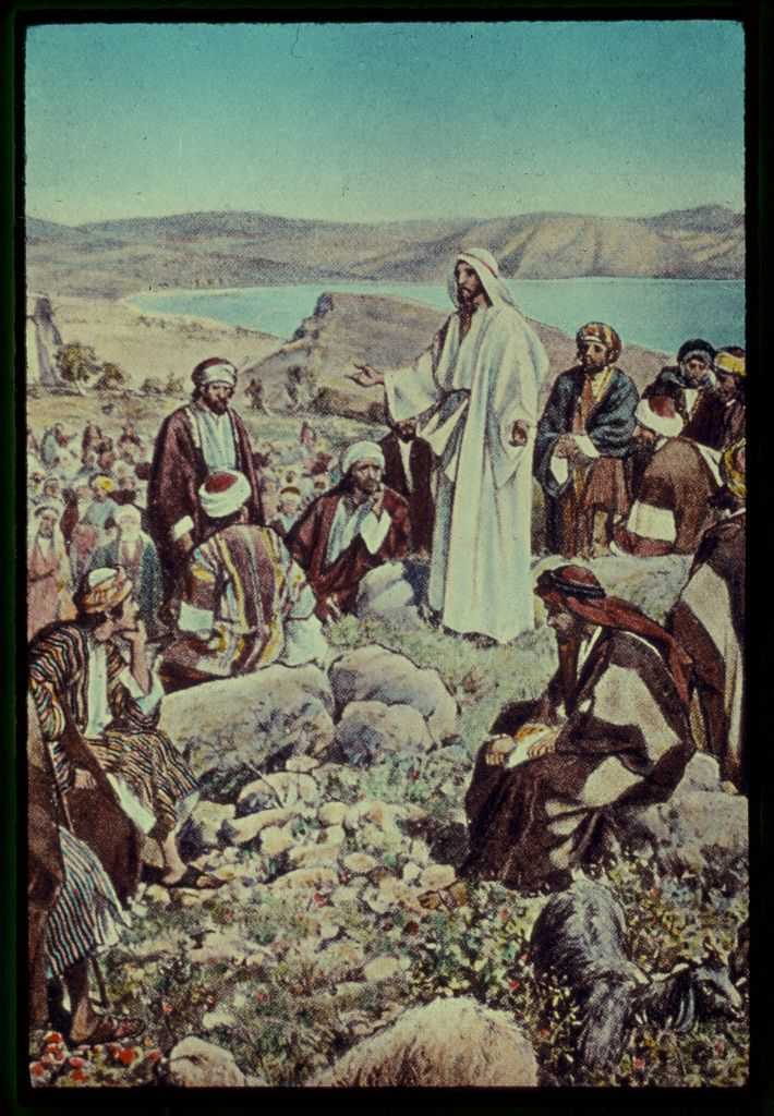 A painting of Jesus standing on a rocky elevated portion of a mountainous region with his arms outstretched speaking to a group of Middle Eastern men during the daytime
