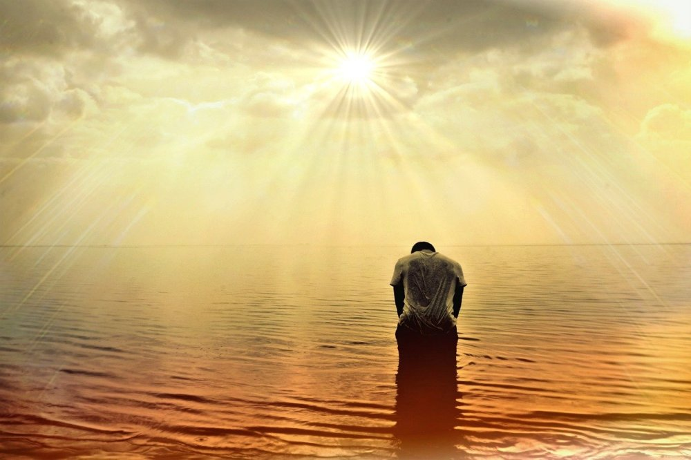 The back side of a man standing in a vast body of somewhat calm water with his head down and the sun with its rays peering out from clouds overhead and an orange hue is lightly cast over the water