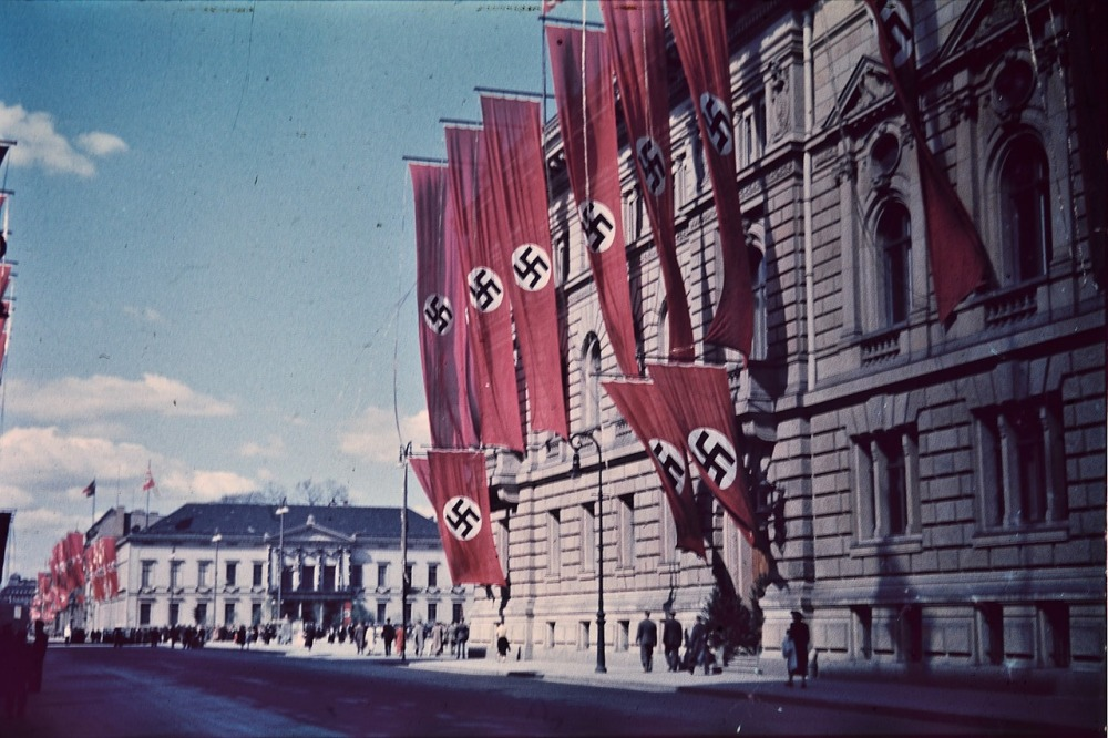 A street in Berlin, Germany with various people walking and red banners and flags displaying a swastika symbol hanging down off the sides of various buildings and a blue lightly clouded sky on the background