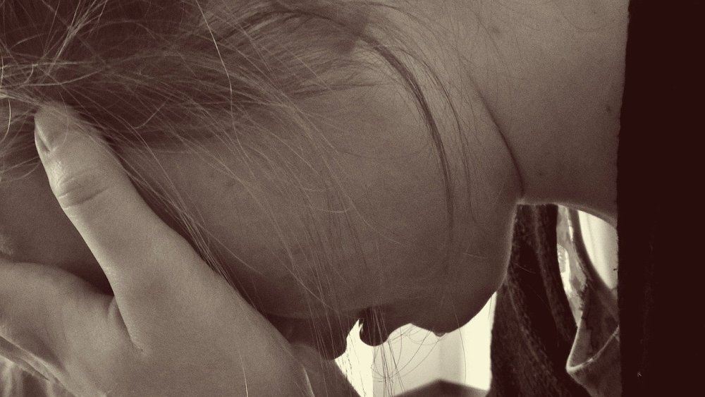Closeup sepia style photo of young woman with head in hands and crying
