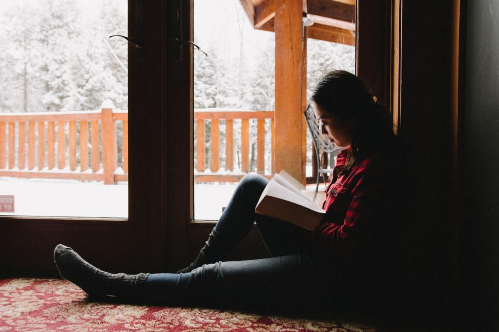 A young woman sitting with one leg outstretched and the other bent to support a book being read while inside a building in front of a pair of doors that open out to a bright, snow covered deck and forest in the background