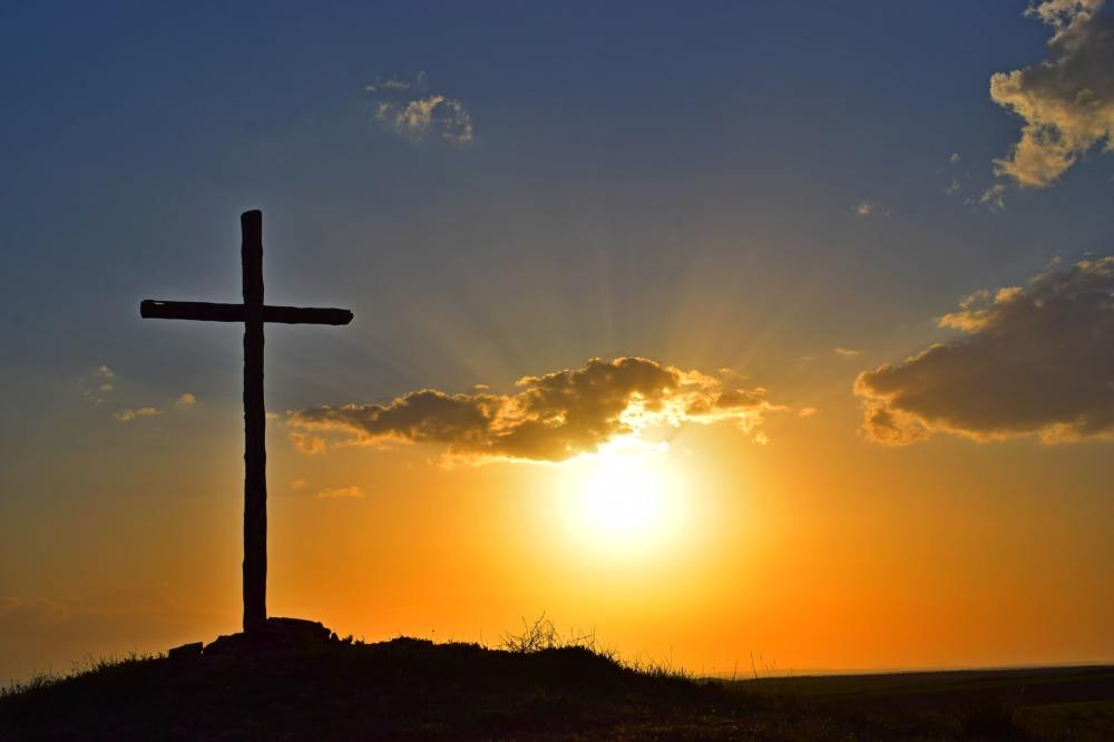 A silhouette of a cross on a small hill with sun, clouds and an orange and blue in the background