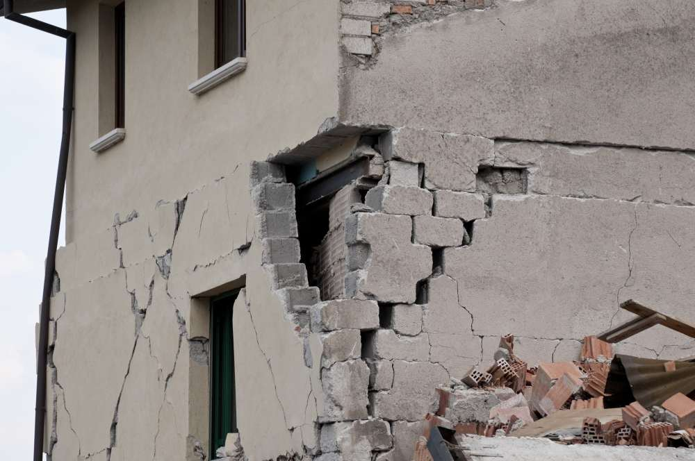 A photo of a close-up of a concrete block building with significant damage a corner of it