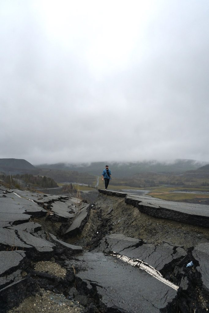 A man with a blue jacket and dark pants walking alongside a collapsed roadway from an earthquake with mountains and heavy fog in the distant background