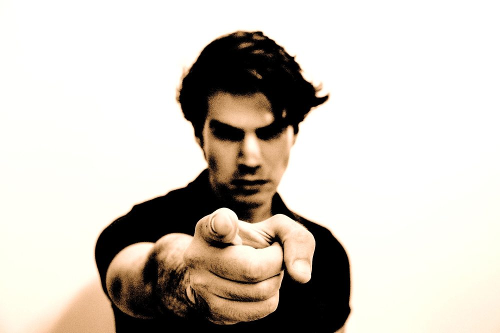 A Caucasian man with dark styled hair and a black shirt looking sternly and pointing index finger at viewer