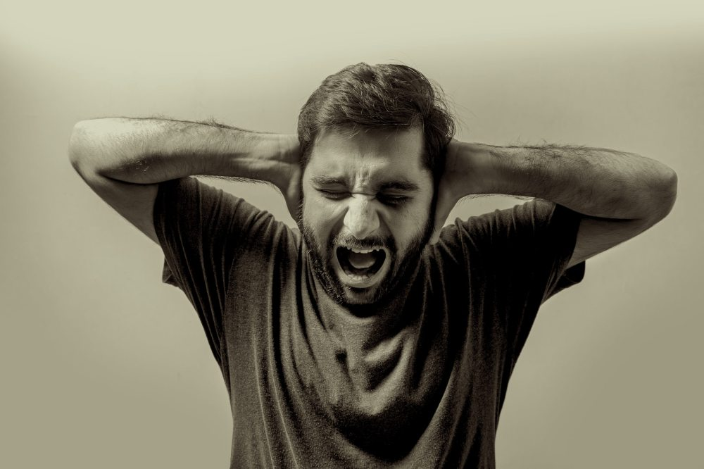 An enhanced black and white photo of a middle aged man with dark hair and beard wearing a dark t-shirt while holding his hands up against his ears and screaming