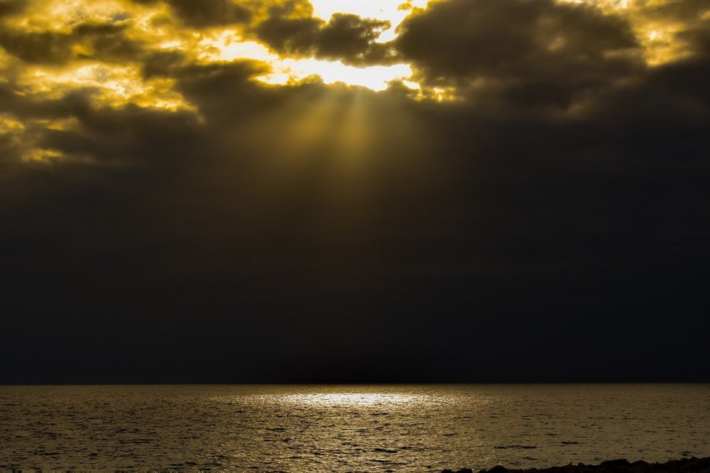 Yellow sunbeams from top of photo streaming down on one area of a large body of water with darkness all around